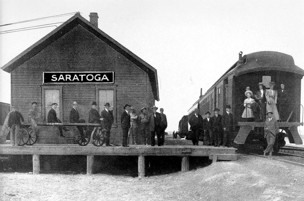Passengers at the Saratoga depot of the Saratoga & Encampment Railway Company. The depot was built in 1915. It was moved in the 1970's by the Saratoga Historical & Cultural Association and now houses the Saratoga Museum.