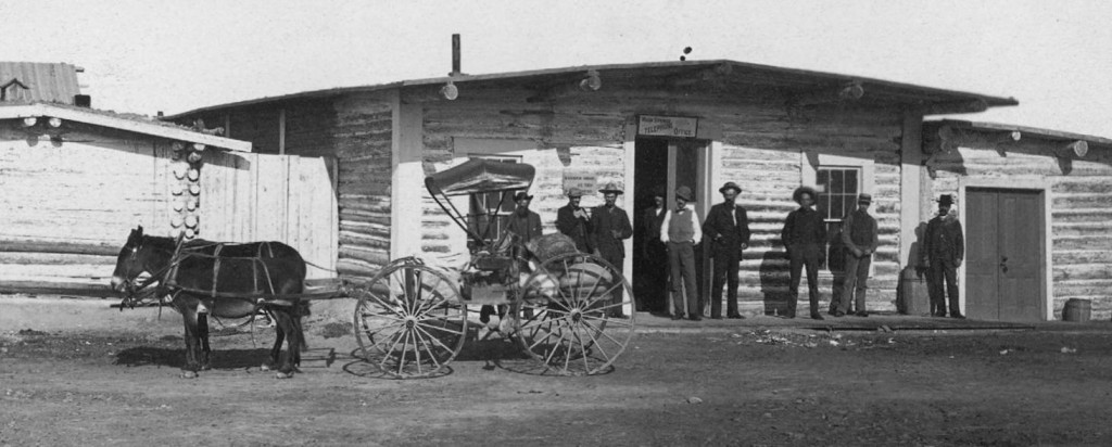 "This early 1880s photograph is the only know picture which shows the name of ""Warm Springs"", which appears above the open door. The log structure was later burned to the ground in 1950 to make room for the Saratoga Inn Saloon."